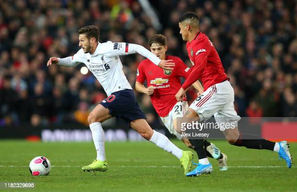 Adam Lallana of Liverpool beats Marcos Rojo of Manchester United during the Premier League match between Manchester United and Liverpool FC at Old...