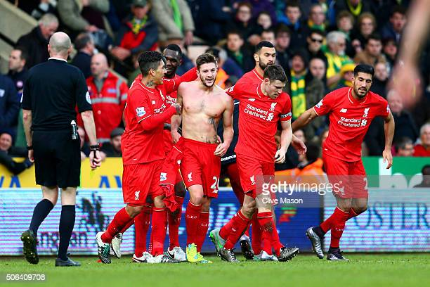 Adam Lallana of Liverpool celebrates scoring his team's fifth goal with team mates during the Barclays Premier League match between Norwich City and...