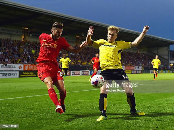 Adam Lallana of Liverpool competes with Damien McCrory of Burton Albion during the EFL Cup match between Burton Albion and Liverpool at the Pirelli...