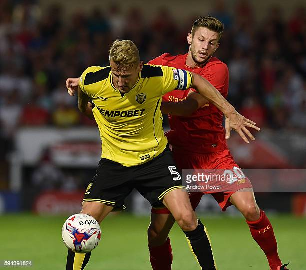 Adam Lallana of Liverpool competes with Kyle McFadzean of Burton Albion during the EFL Cup match between Burton Albion and Liverpool at the Pirelli...
