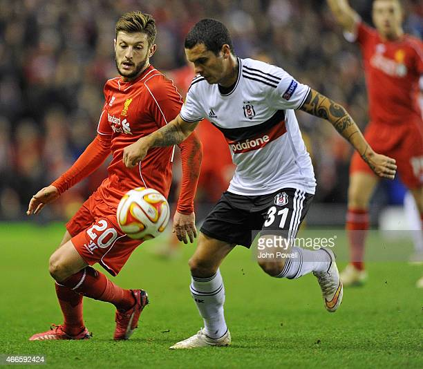 Adam Lallana of Liverpool competes with Ramon Motta of Besiktas during the UEFA Europa League Round of 32 match between Liverpool FC and Besiktas JK...