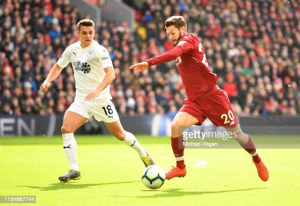 Adam Lallana of Liverpool crosses under pressure from Ashley Westwood of Burnley during the Premier League match between Liverpool FC and Burnley FC...
