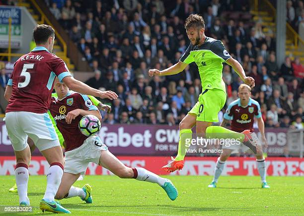 Adam Lallana of Liverpool has a shot on goal blocked by Michael Keane and Ben Mee of Burnley during the Premier League match between Burnley FC and...
