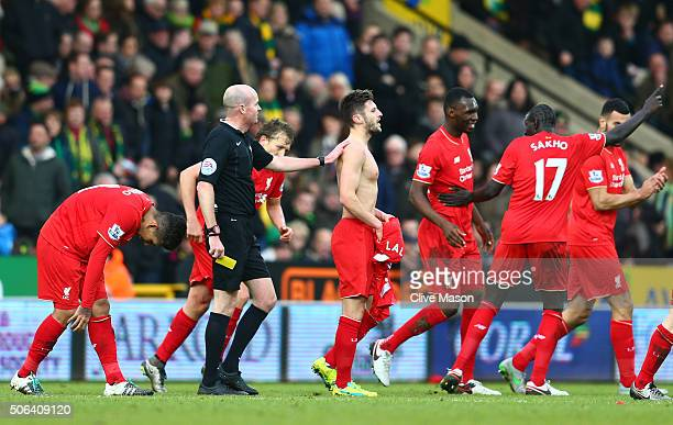 Adam Lallana of Liverpool is shown a yellow card by referee Lee Mason during the Barclays Premier League match between Norwich City and Liverpool at...