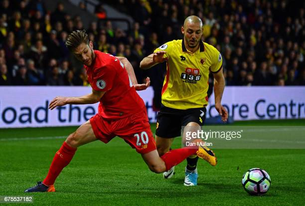 Adam Lallana of Liverpool is tackled by Nordin Amrabat of Watford during the Premier League match between Watford and Liverpool at Vicarage Road on...