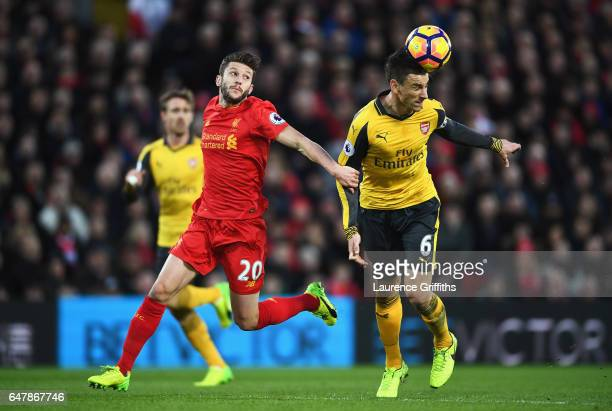 Adam Lallana of Liverpool puts pressure on Laurent Koscielny of Arsenal during the Premier League match between Liverpool and Arsenal at Anfield on...