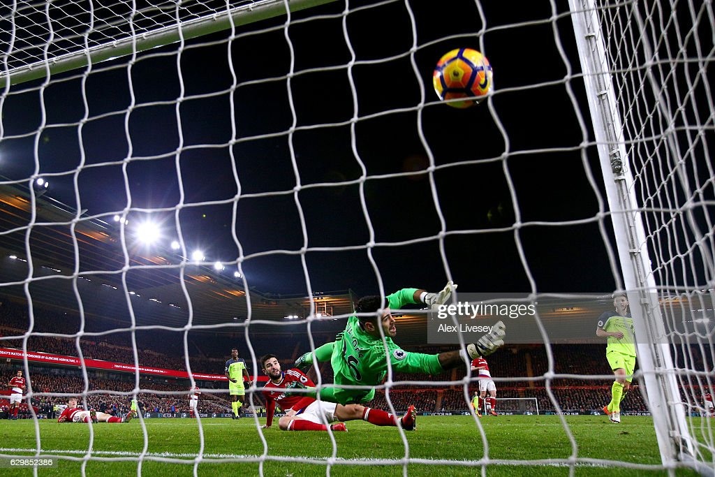 Adam Lallana (R) of Liverpool scores his team's third goal past Victor Valdes of Middlesbrough during the Premier League match between Middlesbrough and Liverpool at Riverside Stadium on December 14, 2016 in Middlesbrough, England.