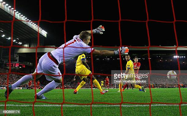 Adam Lallana of Liverpool scores the opening goal past Andris Vanins of FC Sion during the UEFA Europa League group B match between Liverpool FC and...