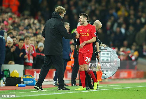 Adam Lallana of Liverpool shakes hands with Jurgen Klopp manager of Liverpool as he is substituted during the Premier League match between Liverpool...