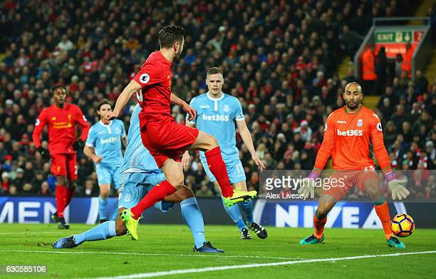 Adam Lallana of Liverpool shoots past Lee Grant of Stoke City to score their first goal during the Premier League match between Liverpool and Stoke...