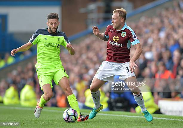 Adam Lallana of Liverpool tackles Scott Arfield of Burnley during the Premier League match between Burnley FC and Liverpool FC at Turf Moor on August...