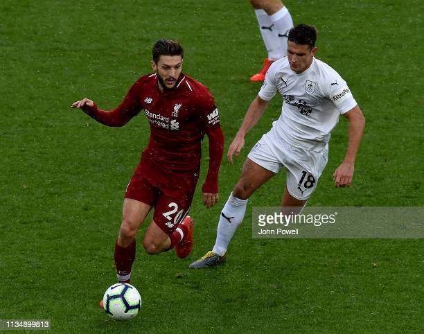Adam Lallana of Liverpool with Astley Westwood of Burnley FC during the Premier League match between Liverpool FC and Burnley FC at Anfield on March...