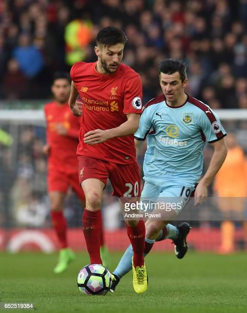 Adam Lallana of Liverpool with joey Barton of Burnley during the Premier League match between Liverpool and Burnley at Anfield on March 12 2017 in...