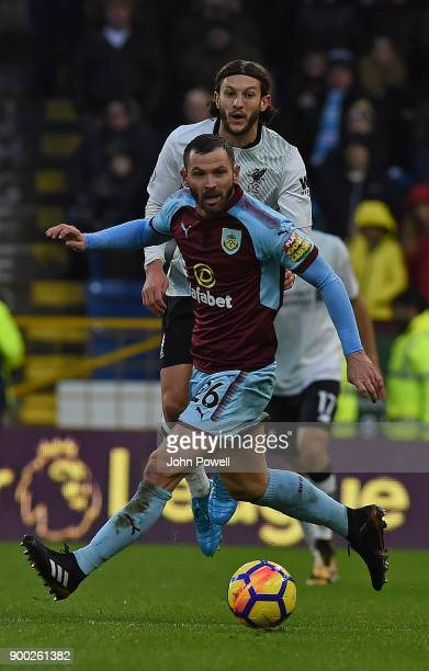 Adam Lallana of Liverpool with PHil Bardsley of Burnley during the Premier League match between Burnley and Liverpool at Turf Moor on January 1 2018...