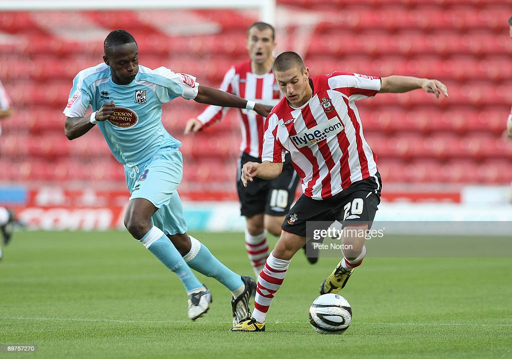Adam Lallana of Southampton attempts to move away from Abdul Osman of Northampton Town during the Carling Cup Round One Match between Southampton and Northampton Town at St Mary's Stadium on August 11, 2009 in Southampton, England. Southampton won the match 2-0.