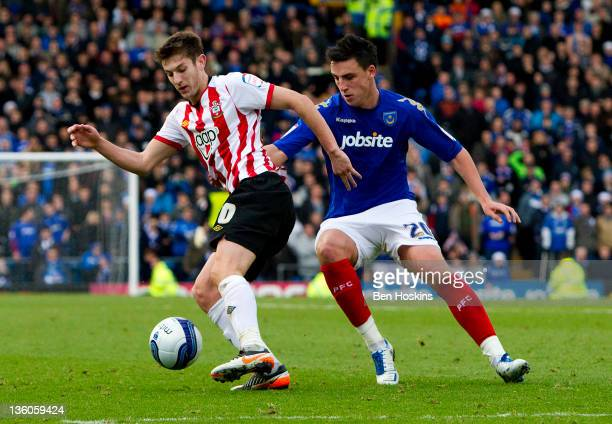 Adam Lallana of Southampton is put under pressure by George Thorne of Portsmouth during the npower Championship match between Portsmouth and...