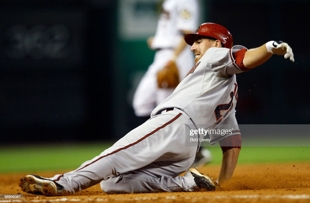 Adam LaRoche #25 of the Arizona Diamondbacks slides safely into third base after hitting a triple in the fifth inning against the Houston Astros as third baseman Geoff Blum awaits the throw at Minute Maid Park on May 6, 2010 in Houston, Texas.