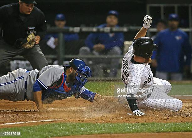 Adam LaRoche of the Chicago White Sox scores a run in the 6th inning as Dioner Navarro of the Toronto Blue Jays attempts the tag at US Cellular Field...