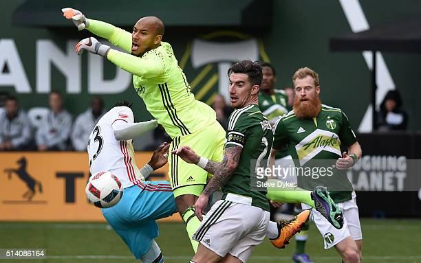 Adam Larsen Kwarasey of Portland Timbers knocks the ball away from Kei Kamara of Columbus Crew as Liam Ridgewell and Nat Borchers of Portland Timbers...