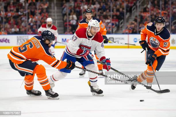 Adam Larsson and Ryan NugentHopkins of the Edmonton Oilers hassle Kenny Agostino of the Montreal Canadiens during the third period at Rogers Place on...