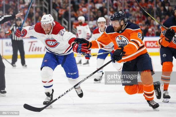 Adam Larsson of the Edmonton Oilers battles against Nicolas Deslauriers of the Montreal Canadiens at Rogers Place on December 23 2017 in Edmonton...