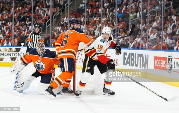 Adam Larsson of the Edmonton Oilers battles Matthew Tkachuk of the Calgary Flames in the season opener at Rogers Place on October 4 2017 in Edmonton...