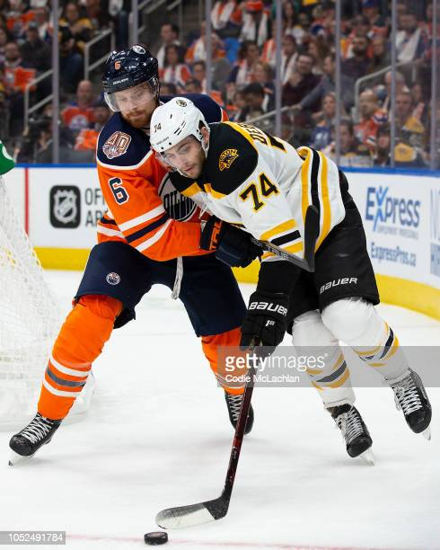 Adam Larsson of the Edmonton Oilers hassles Jake DeBrusk of the Boston Bruins at Rogers Place on October 18 2018 in Edmonton Canada