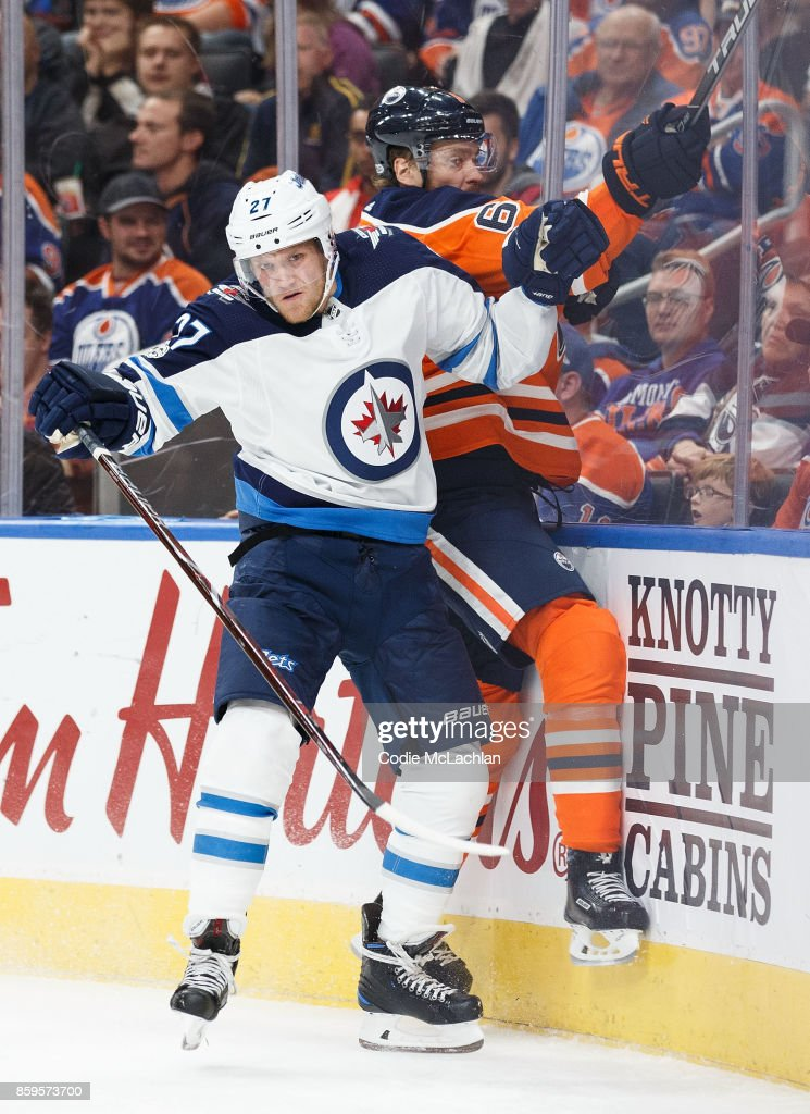 Adam Larsson #6 of the Edmonton Oilers is hit by Nikolaj Ehlers #27 of the Winnipeg Jets at Rogers Place on October 9, 2017 in Edmonton, Canada.
