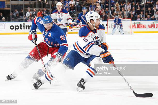 Adam Larsson of the Edmonton Oilers skates with the puck against Rick Nash of the New York Rangers at Madison Square Garden on November 3 2016 in New...