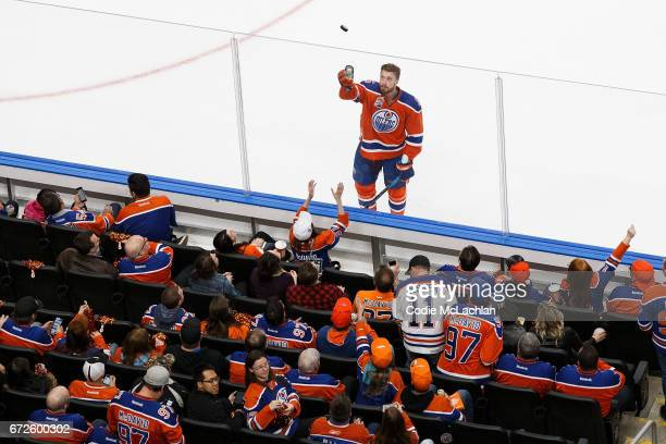 Adam Larsson of the Edmonton Oilers throws a puck to a fan during warmup against the San Jose Sharks in Game Five of the Western Conference First...