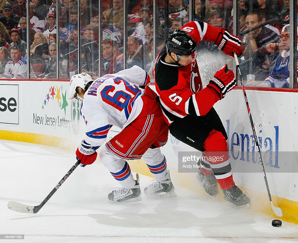 Adam Larsson #5 of the New Jersey Devils avoids a check by Carl Hagelin #62 of the New York Rangers during the game at the Prudential Center on March 19, 2013 in Newark, New Jersey.