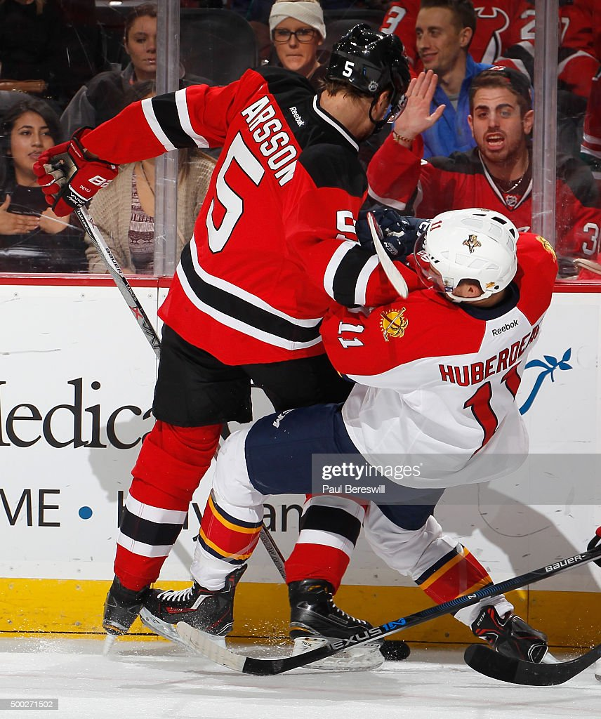 Adam Larsson #5 of the New Jersey Devils knocks Jonathan Huberdeau #11 of the Florida Panthers to the ice in the second period of an NHL hockey game at Prudential Center on December 6, 2015 in Newark, New Jersey. Devils won 4-2.