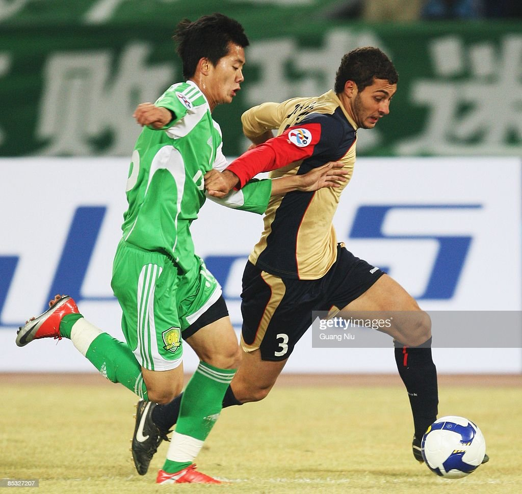 Adam Leonard D'Apuzzo (R) of Newcastle Jets and Huang Bowen of Beijing Guoan fight for the ball during the AFC Champions League Group E match between Beijing Guoan and the Newcastle Jets at Beijing Worker's Stadium on March 10, 2009 in Beijing, China.