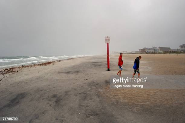 Adam Lesch and Brooks Bailey stand in the rain and wind on the beach before Tropical Storm Ernesto August 31 in Wrightsville Beach North Carolina The...