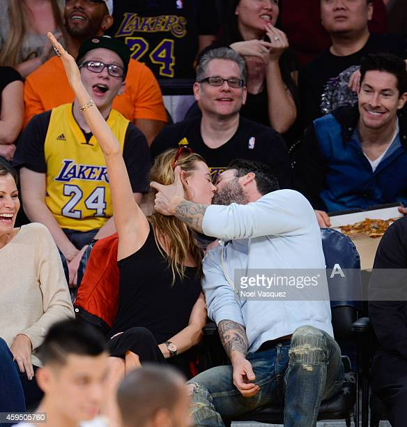 Adam Levine and Behati Prinsloo kiss at a basketball game between the Denver Nuggets and the Los Angeles Lakers at Staples Center on November 23 2014...
