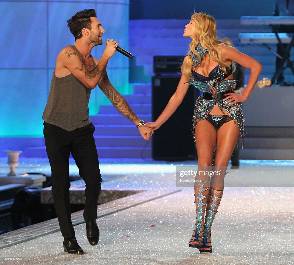 Adam Levine of Maroon 5 holds hands with Model Anne V as she walks the runway during the 2011 Victoria's Secret Fashion Show at the Lexington Avenue Armory on November 9, 2011 in New York City.