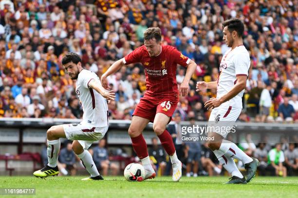 Adam Lewis of Liverpool battles for the ball with Daniel Devine and Anthony O'Conner of Bradford City during the PreSeason Friendly match between...