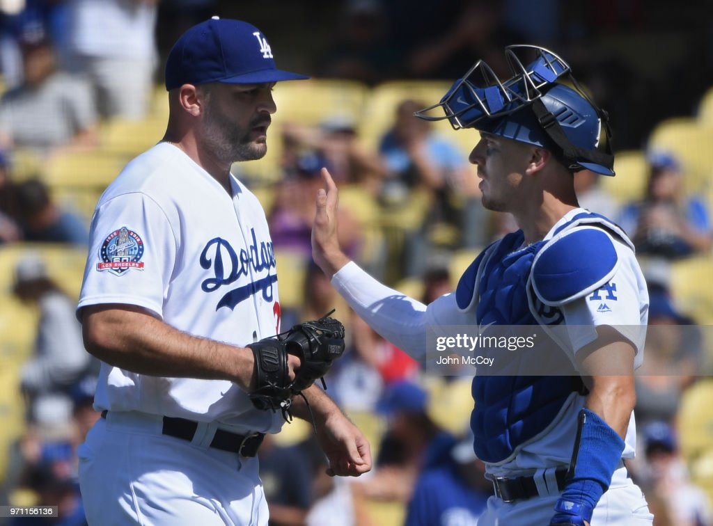 Adam Liberatore #36 of the Los Angeles Dodgers is congratulated by Austin Barnes #15 after defeating the Atlanta Braves at Dodger Stadium on June 10, 2018 in Los Angeles, California. Dodgers won 7-2.