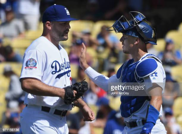 Adam Liberatore of the Los Angeles Dodgers is congratulated by Austin Barnes after defeating the Atlanta Braves at Dodger Stadium on June 10 2018 in...