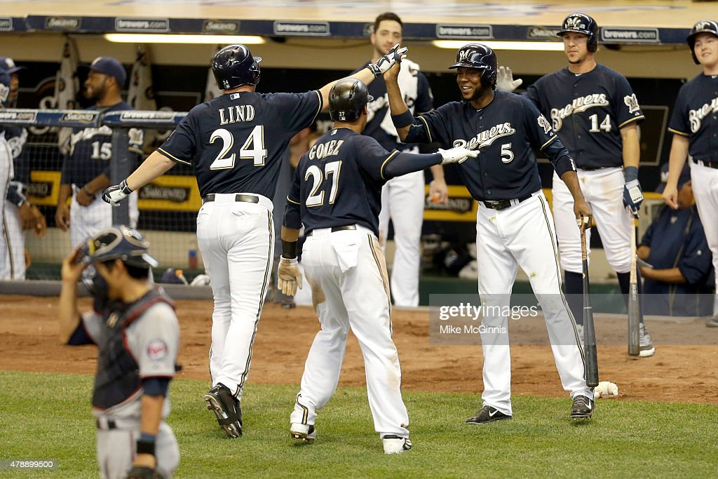 Adam Lind #24 of the Milwaukee Brewers celebrates with Hector Gomez #5 and Carlos Gomez #27 a two run homer in the eighth inning against the Minnesota Twins during the Interleague game at Miller Park on June 28, 2015 in Milwaukee, Wisconsin.