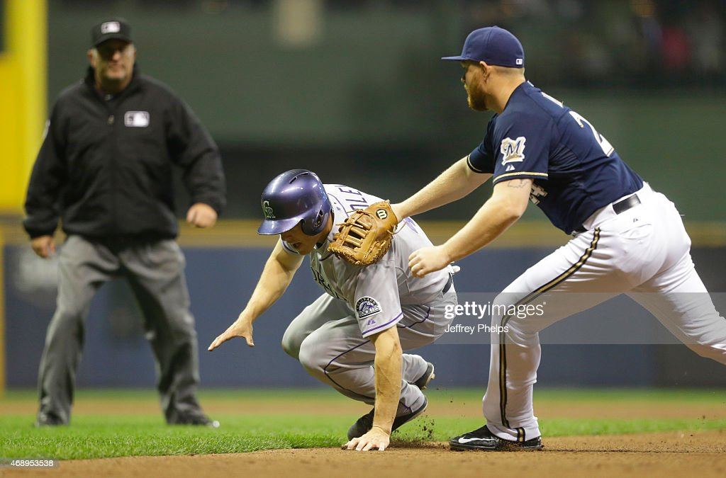 Adam Lind #24 of the Milwaukee Brewers tags out Nick Hundley #4 of the Colorado Rockies during a rundown in the fifth inning at Miller Park on April 8, 2015 in Milwaukee, Wisconsin.