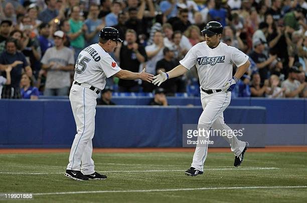 Adam Lind of the Toronto Blue Jays celebrates his home run with Third Base Coach Brian Butterfield during MLB game action against the Baltimore...
