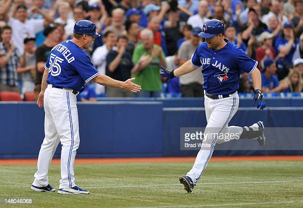 Adam Lind of the Toronto Blue Jays celebrates his home run with Third Base Coach Brian Butterfield during MLB game action against the Kansas City...