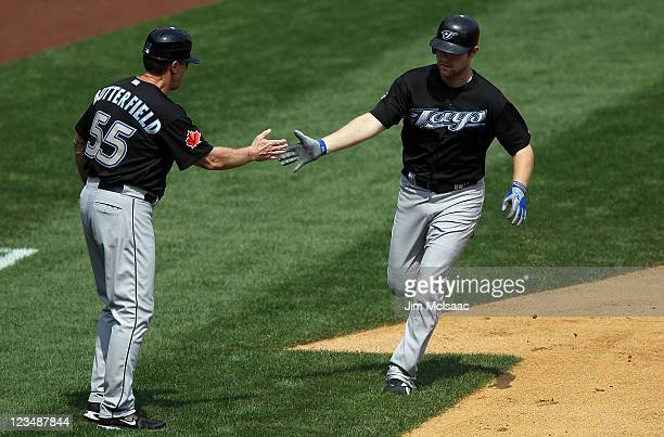 Adam Lind of the Toronto Blue Jays celebrates his second inning home run against the New York Yankees with third base coach Brian Butterfield on...