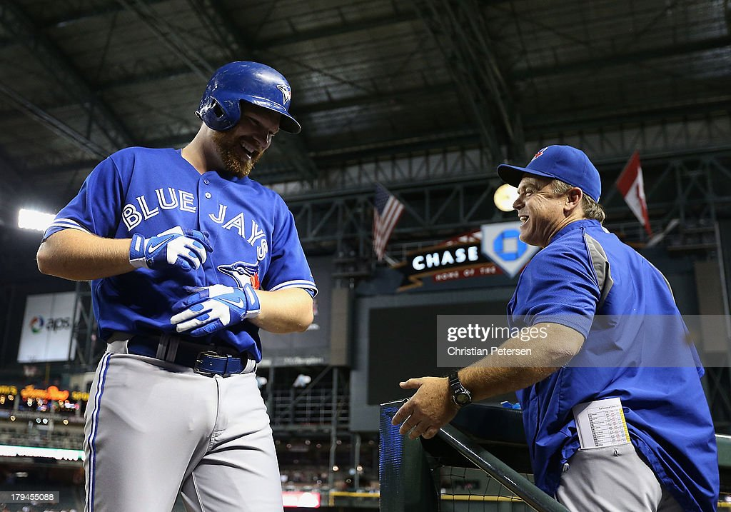 Adam Lind #26 of the Toronto Blue Jays high-fives manager John Gibbons #5 after hitting a solo home run against the Arizona Diamondbacks during the ninth inning of the interleague MLB game at Chase Field on September 3, 2013 in Phoenix, Arizona.