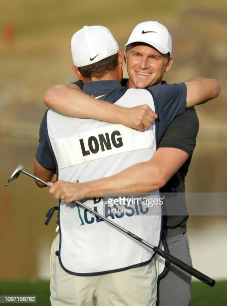 Adam Long of the United States hugs his caddie Matt Olsen after making the winning putt on the 18th green during the final round of the Desert...