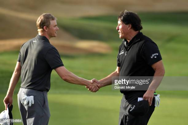 Adam Long of the United States shakes hands with Phil Mickelson of the United States after winning the final round of the Desert Classic at the...
