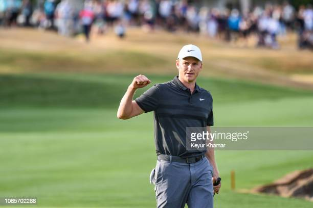 Adam Long pumps his fist and celebrates his one stroke victory after making a winning birdie putt on the 18th hole green during the final round of...