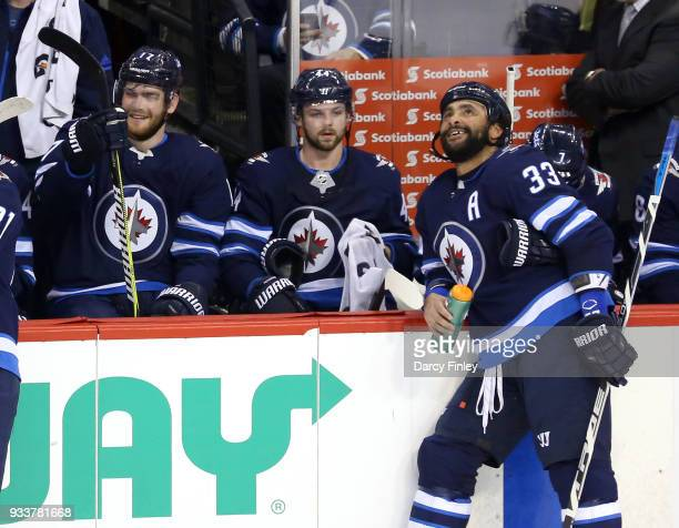 Adam Lowry and Dustin Byfuglien of the Winnipeg Jets share a laugh at the bench during a first period stoppage in play against the Dallas Stars at...