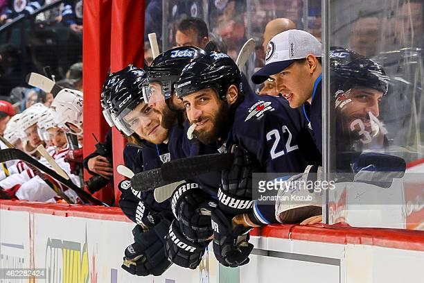 Adam Lowry Anthony Peluso Chris Thorburn and Michael Hutchinson of the Winnipeg Jets look on from the bench during the shootout against the Arizona...